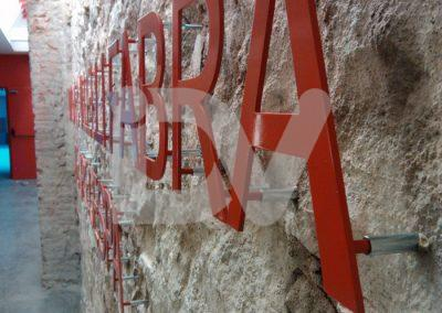 Letras de aluminio con separadores a pared de piedra